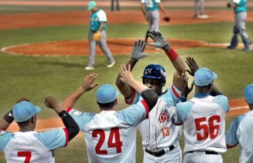 El avileño Yoelvis Fiss dispara jonrón con bases llenas y decide el partido frente a La Isla de la Juventud y es felicitado por sus compañeros en el estadio José Ramón Cepero sede del primer partido de la gran final de la 54 Serie Nacional de Béisbol, en Ciego de Ávila, Cuba el 3 de abril de 2015. AIN FOTO/ Osvaldo GUTIÉRREZ GÓMEZ