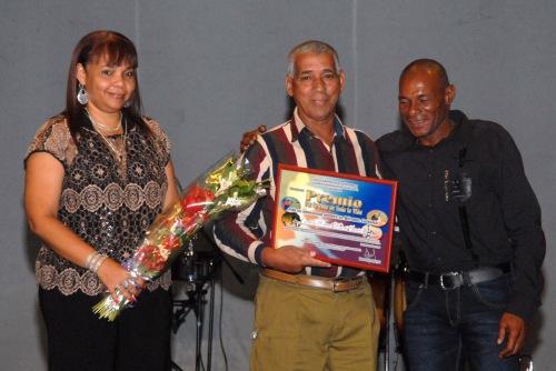 Carlos Martí (C), director del equipo Granma de pelota, recibió un Premio Por la obra de toda la vida, de manos del Campeón Olímpico Ermidelio Urrutia (D), gloria del béisbol, y de Sara Blanco, jefa del departamento ideológico del Comité Provincial del Partido Comunista de Cuba (PCC), en la Primera Gala del Béisbol de la provincia de Granma, efectuada en el teatro Bayamo de la ciudad homónima, Cuba, el 6 de junio de 2015. AIN FOTO/Armando Ernesto CONTRERAS TAMAYO/sdl