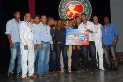 Equipo de pelota del municipio Yara posa junto al Campeón Olímpico Ermidelio Urrutia (C Izq., camisa negra), junto con el  reconocimiento por ser el campeón de la 39 serie provincial de béisbol, en la Primera Gala del Béisbol de la provincia de Granma, efectuada en el teatro Bayamo de la ciudad homónima, Cuba, el 6 de junio de 2015. AIN FOTO/Armando Ernesto CONTRERAS TAMAYO/sdl